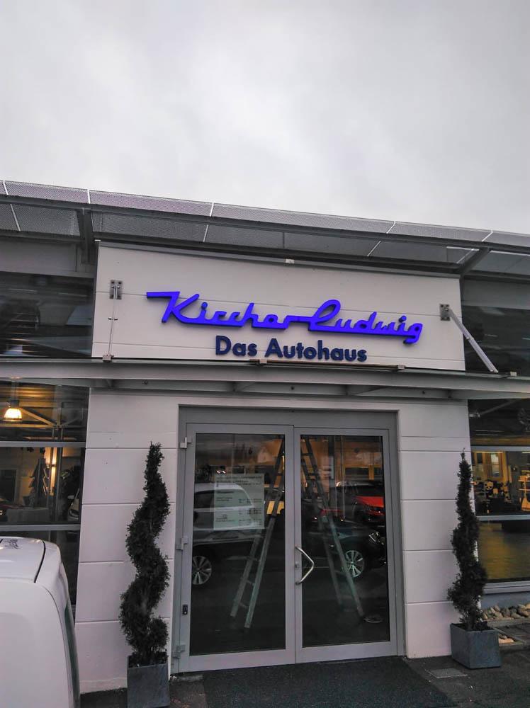 Schild mit Logo über Haupteingang des Autohauses Kircher Ludwig