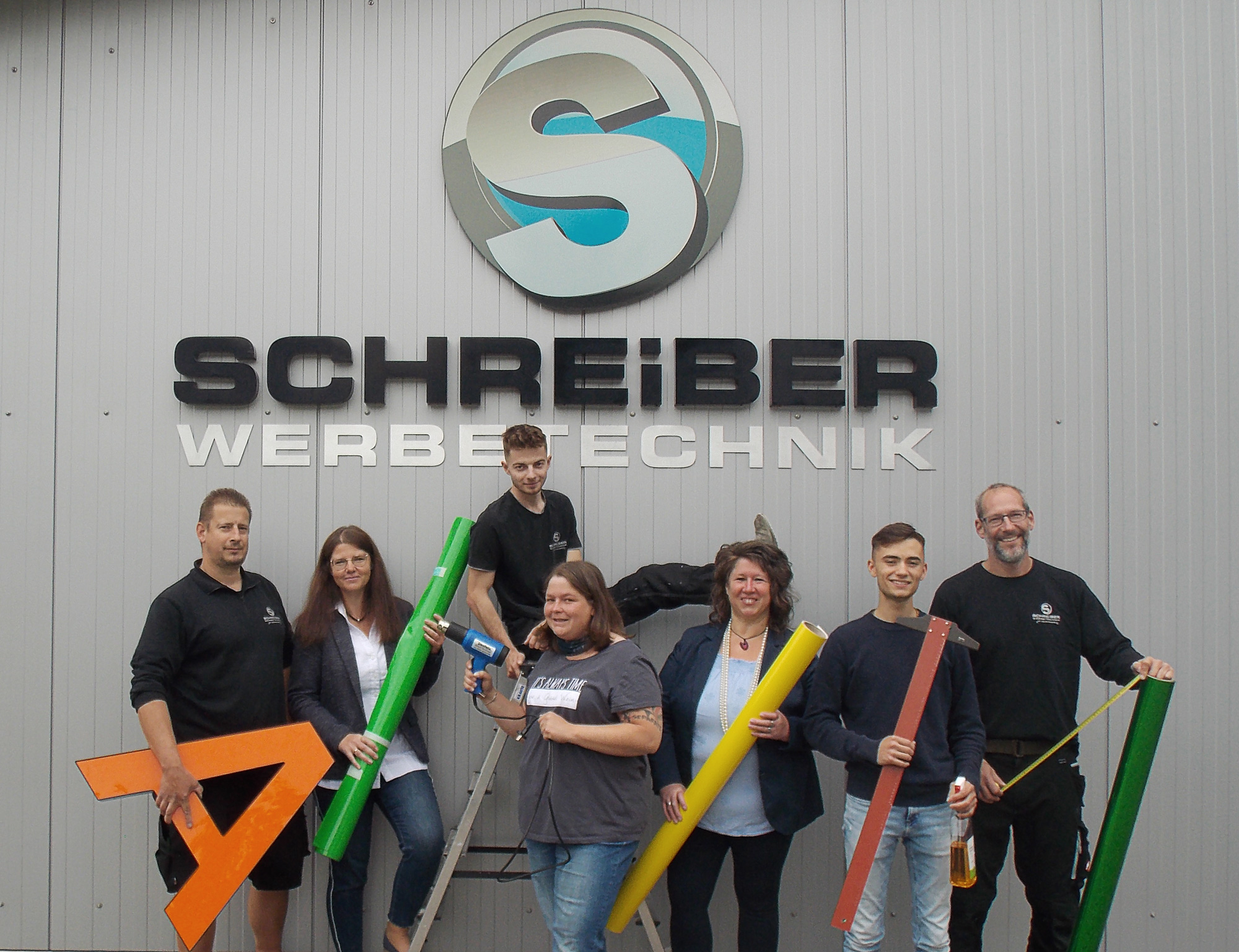 Das Team von Schreiber Werbetechnik vor dem Firmenschild